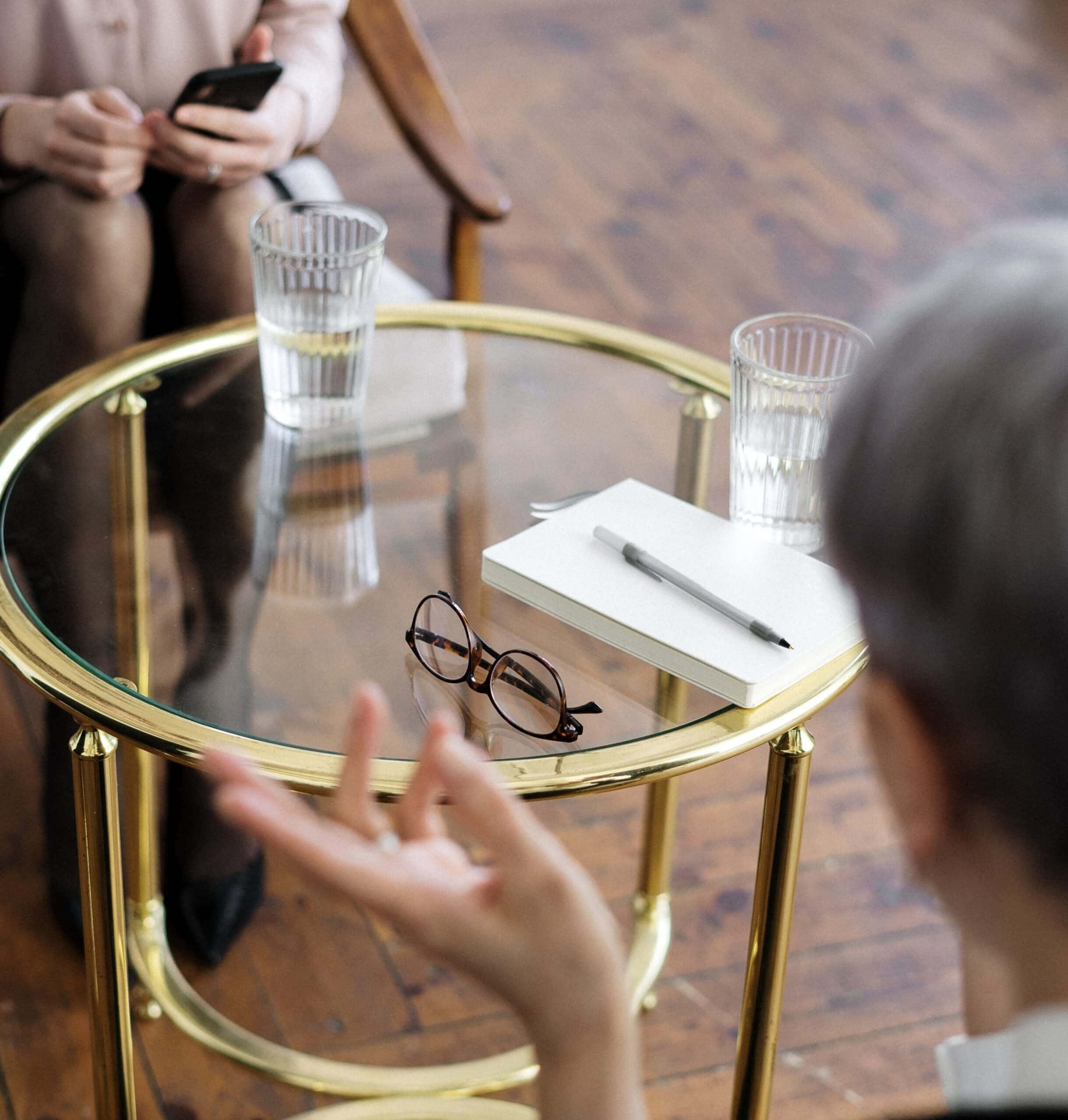 Two women talking with a table between them- Pexels