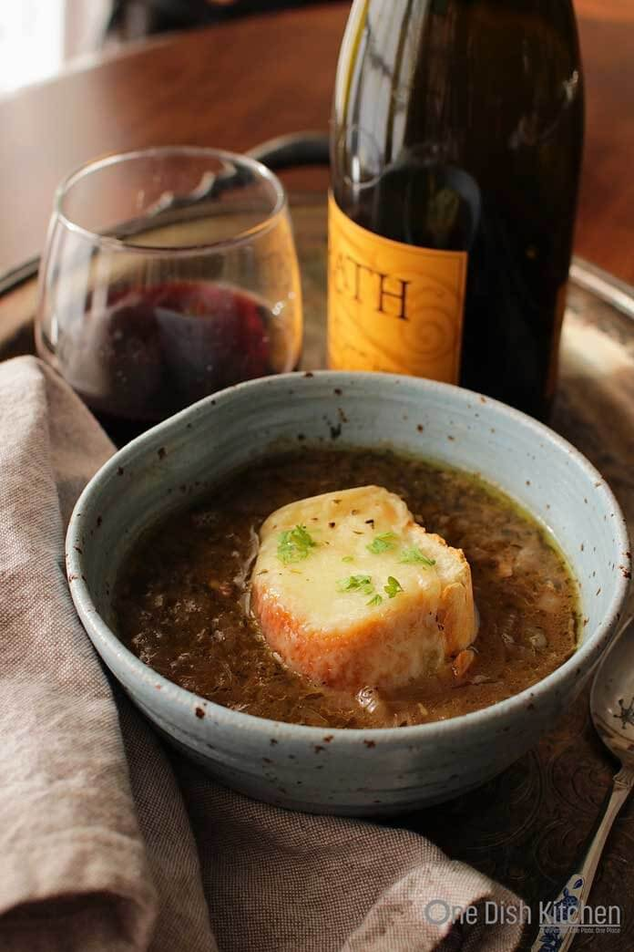 A bowl of french onion soup on a metal tray with a glass and bottle of red wine and a spoon