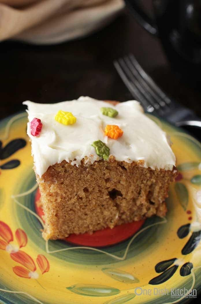 A square slice of a pumpkin bar with cream cheese frosting and fall sprinkles shaped as leaves on a plate