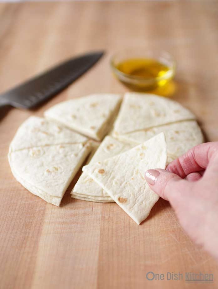 The stack of fresh flour tortilla cut into eight slices like a pizza on a wooden cutting board next to a large knife and a small bowl of olive oil