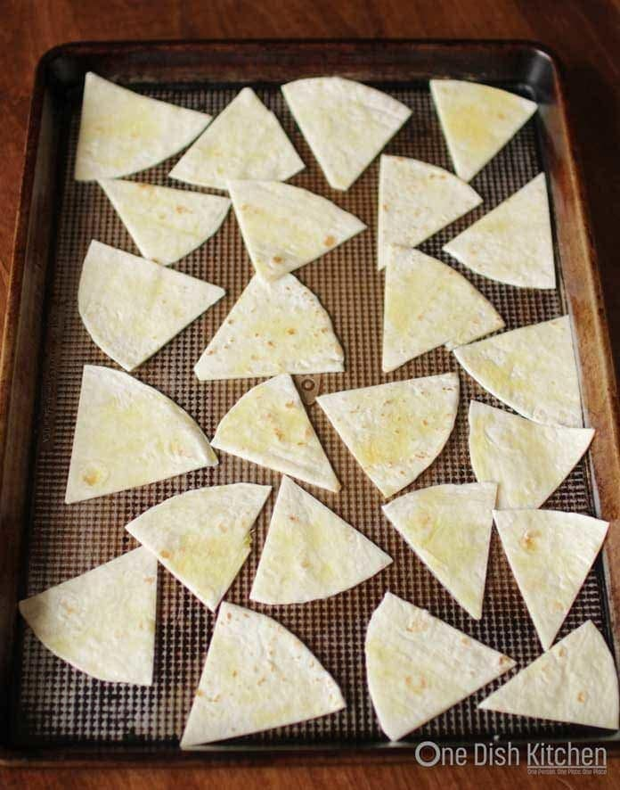 tortilla sliced into wedges on a baking tray ready to go into the oven