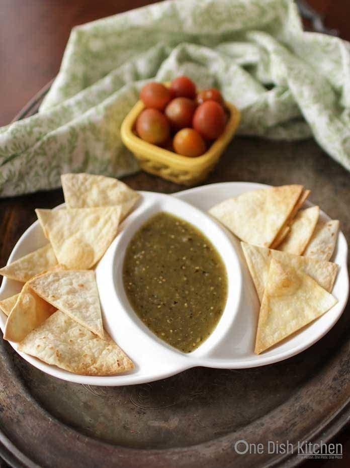 Homemade tortilla chips with green salsa dip on a serving tray