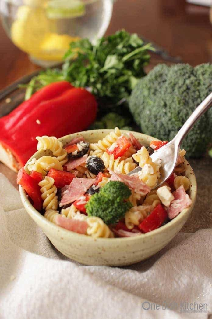 bowl of pasta salad with italian dressing and a fork with salami, olives, broccoli | one dish kitchen