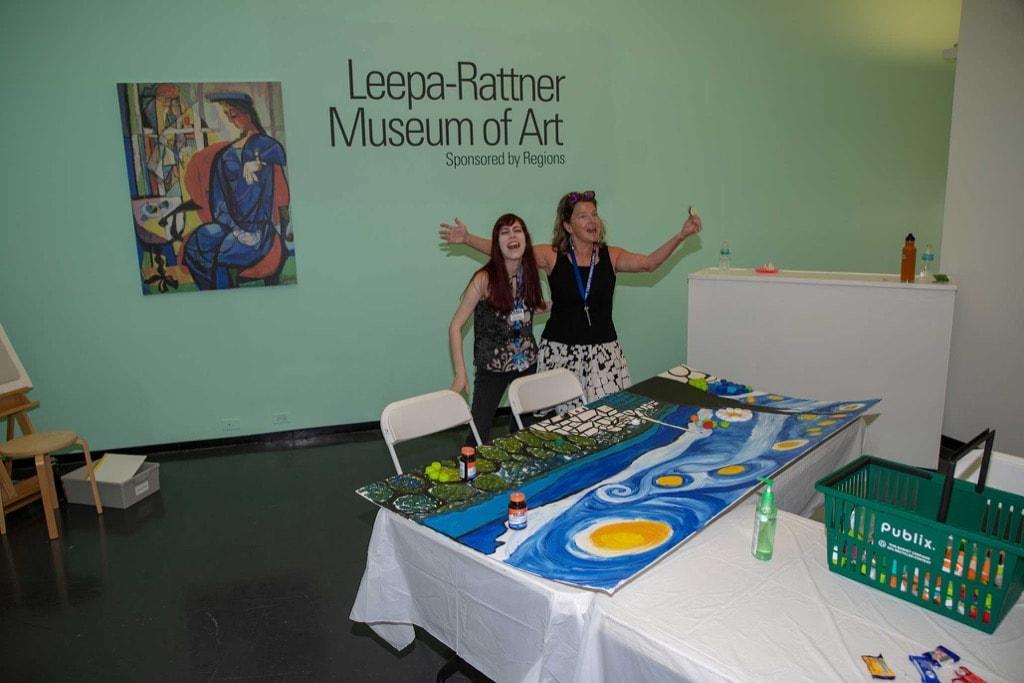 Leepa Ratner Museum volunteers stand by table