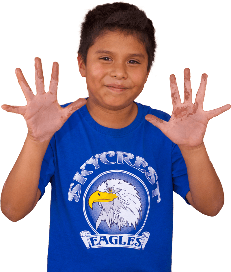Middle school student shows off clay on his hands.