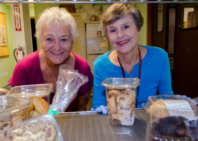 Two senior women enjoy volunteering at RCS Food Bank.