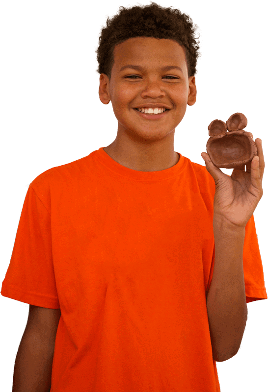 Middle school student shows off his clay sculpture.