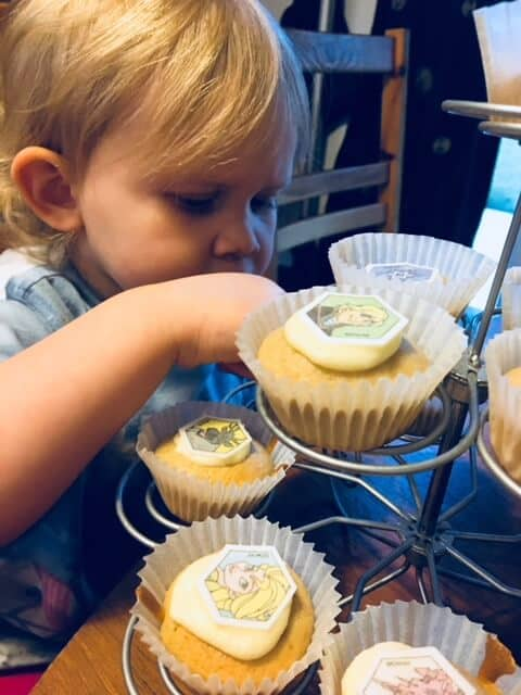 baby girl putting the toppers on the cupcakes