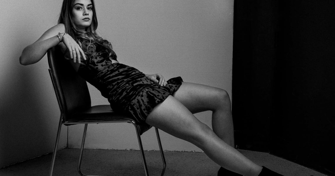 Stonetree Creative - Black and white image of a woman in a black dress lounging in a chair