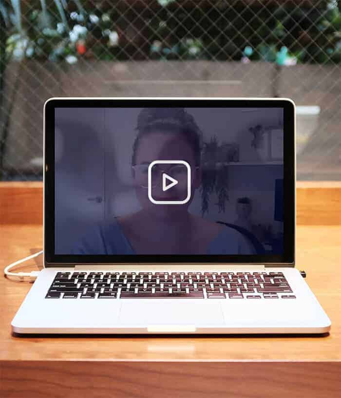 Laptop on table with video play button