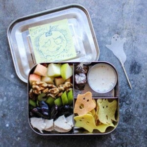 All the elements of a waldorf salad deconstructed and arranged in a bento box with dressing on the side for easy dipping!