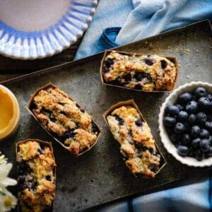 blueberry quick bread mini loaves on tray with fresh blueberries, spreadable honey, and flowers
