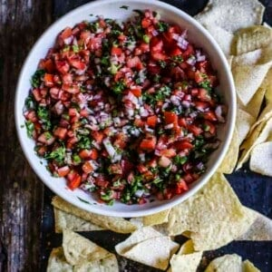 A white bowl filled with pico de gallo. Finely diced tomatoes, red onion, cilantro, jalapeño, and citrus juice. There are tortilla chips around the bowl.