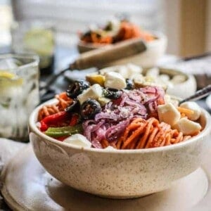 A bowl of red lentil pasta that has been tossed with pizza sauce and then piled high with roasted peppers, onions, artichokes, and black olives.