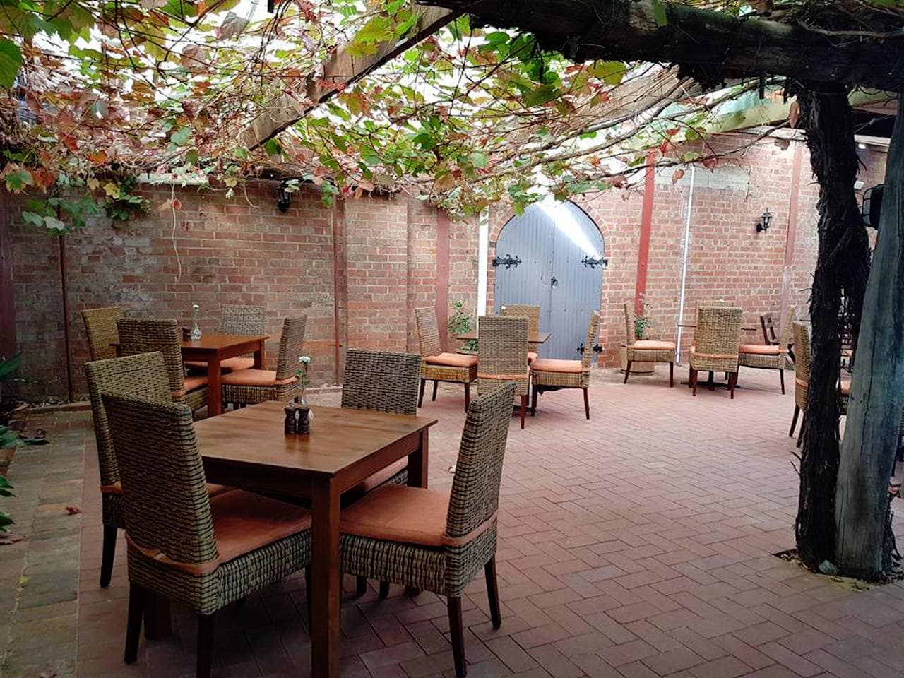 Tables And Rattan Chairs In An Open Area Under A Ceiling Full of Leaves With Brick Wall