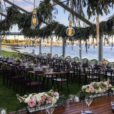 Beautiful Outdoor River-side Wedding Dining Room Setting With Wooden Tables, Large Hanging Light Bulbs And Trees. Roses Sitting On Table In The Foreground.