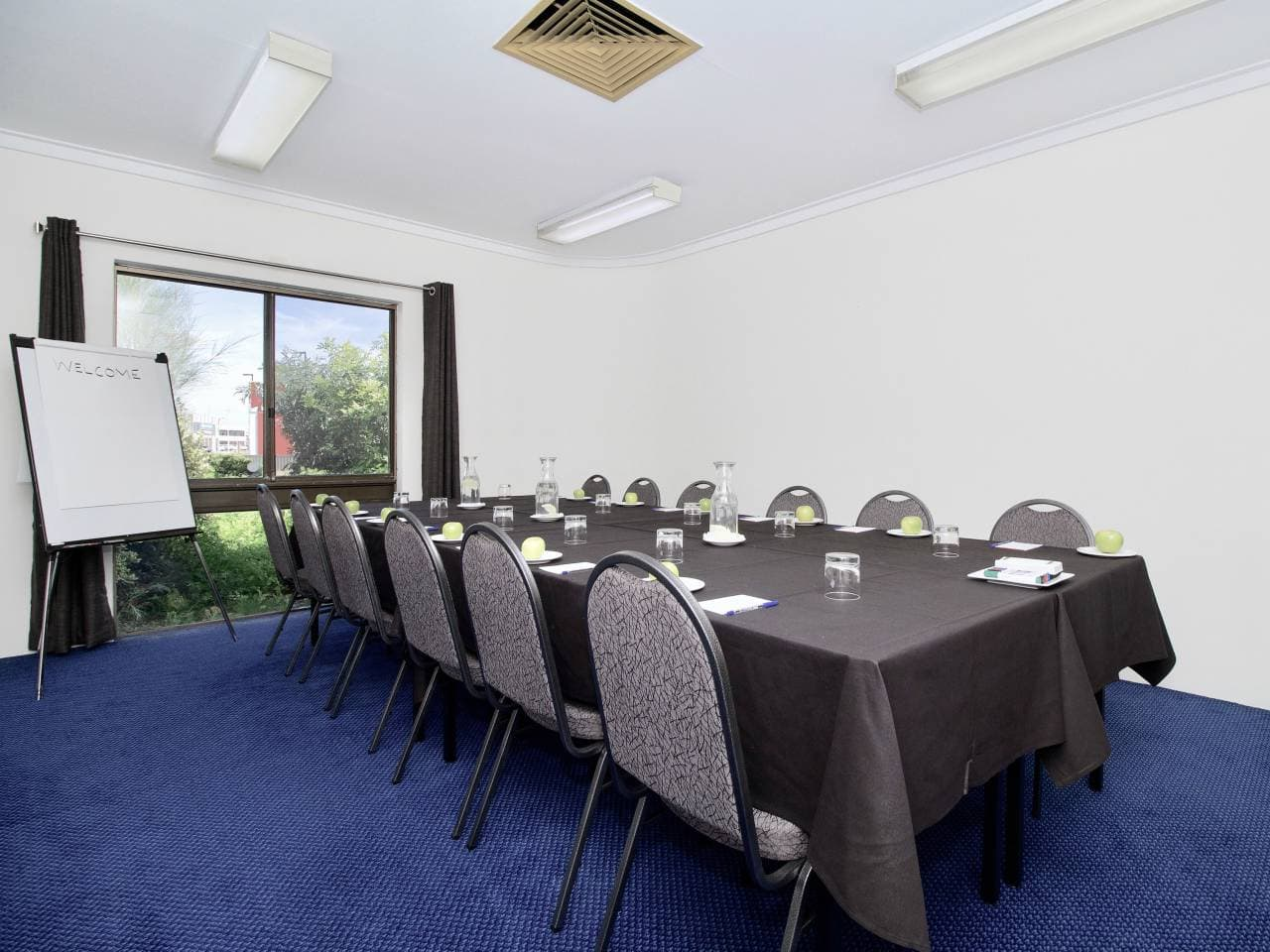 Tables And Chairs Inside The Function Room With Projection Screen
