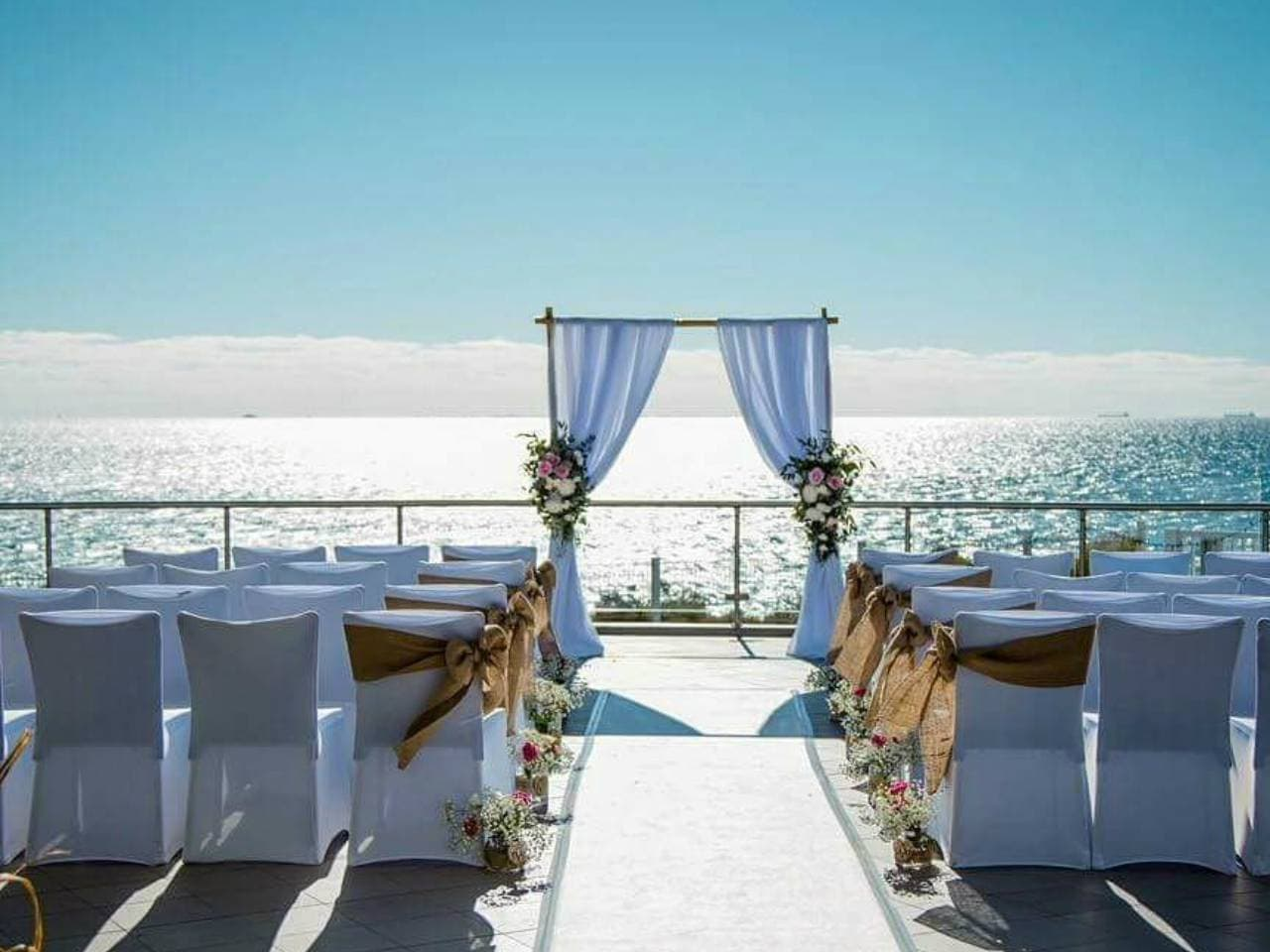 A Alter Leading Up to the Sea With White Chairs For The Guests.