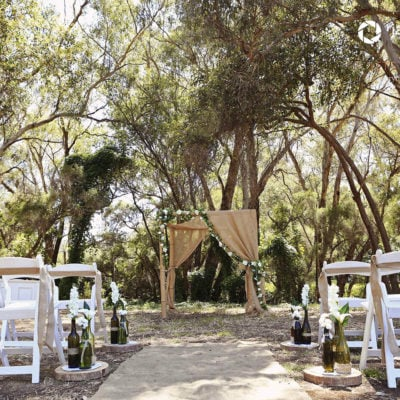 Beautifully adorned arbour with flowers and cloth surounded with white seats facing a forest backdrop