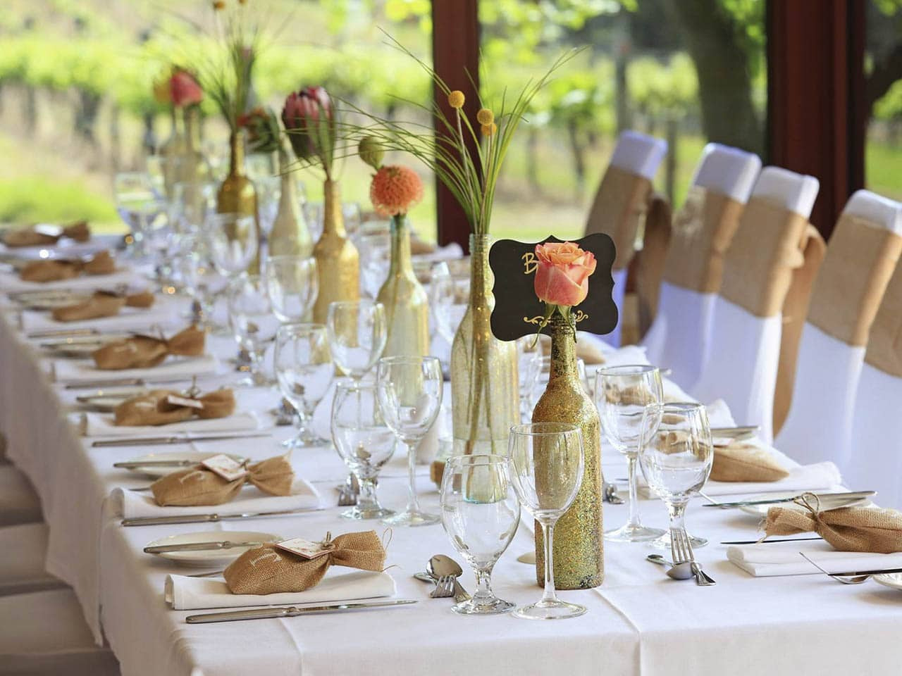 Dining setting with a long table and white table cloth, gold ribbons and gifts on table mats. Roses decorate the table in wine bottles.