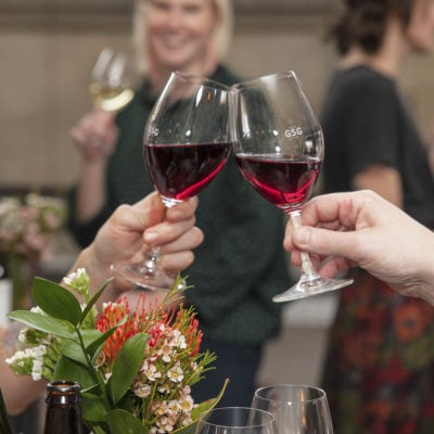 Red wine glass toast with smiling guests in background