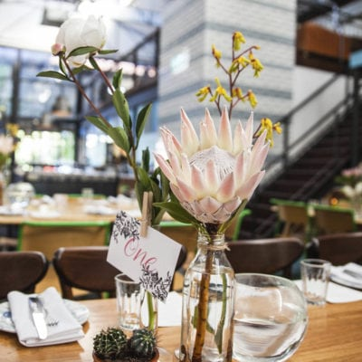 Wedding flower arrangement on table, with blurred empty cafe backdrop
