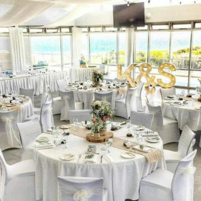 A Bright Open Room, With White Chairs And Round Tables With A Ocean View.