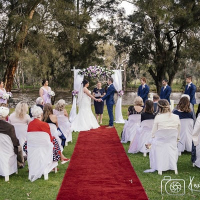 A beautiful wedding with celebrant, wedding couple and guests at the end of a red carpet. Guests sit in white chairs facing the couple with bridesmaids on left and bridegrooms on right with a river and fauna as a backdrop