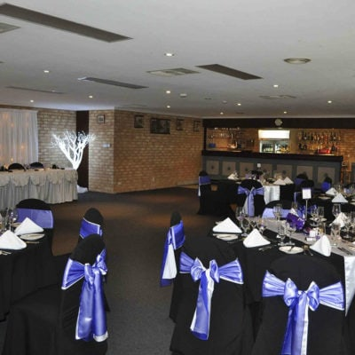 Tables And Chairs In Banquet Style Inside The Function Room With Mini Bar
