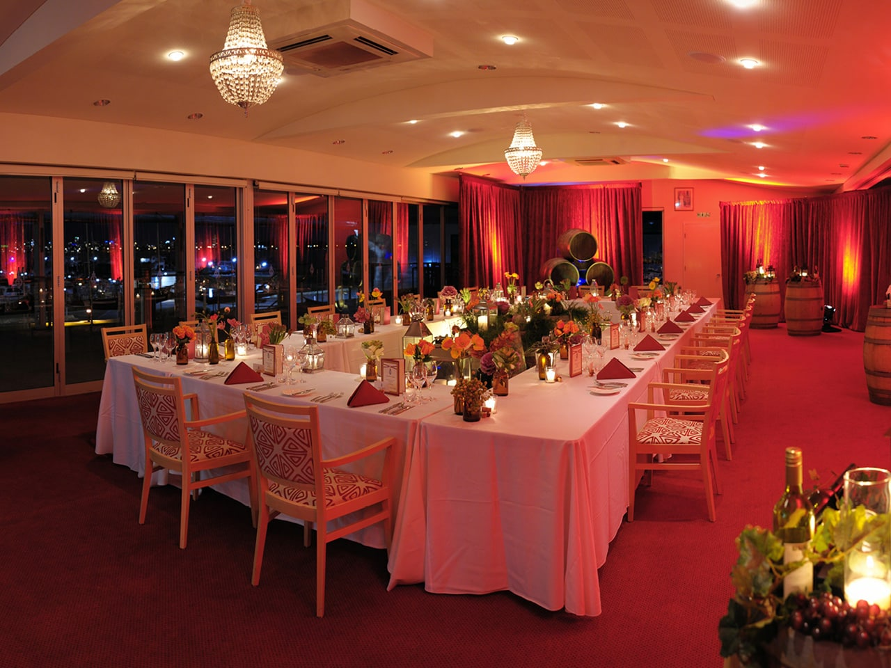 Tables And Chairs In A U-shape Style With Centerpieces, Candle Lit And Red Lightning Inside The Entire Function Room