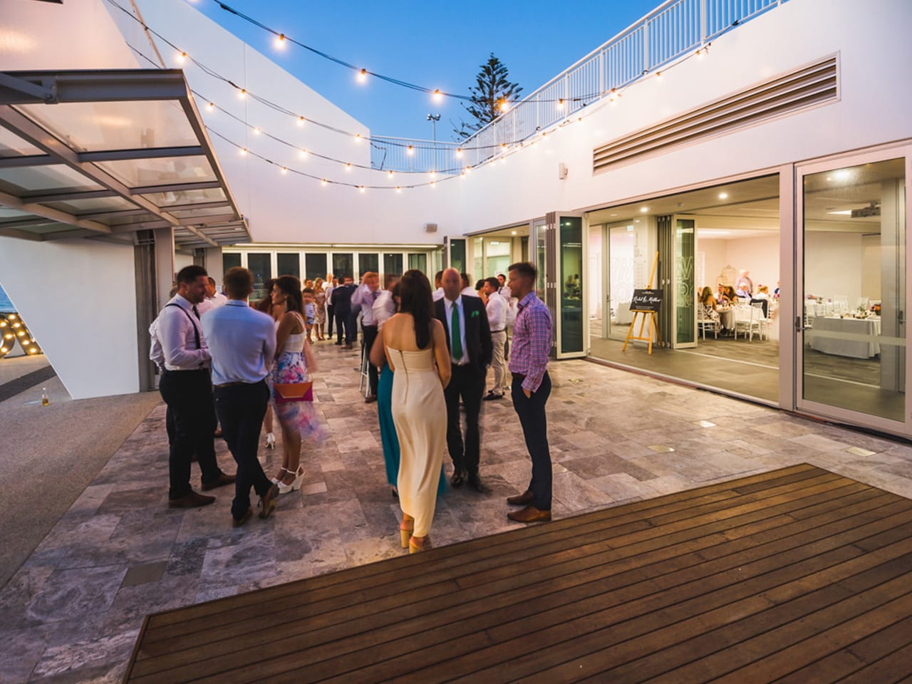 Open Air Function Room Extension With String Lights And People Gathering In Dusk