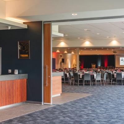 Distant View OF The Inside Of Function Room From Outside With Banquet Setup, Stage And Projection Screen