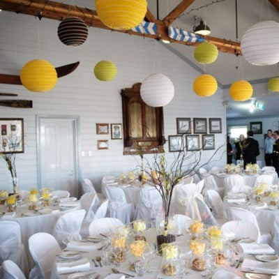 Chairs And Tables In Banquet Style With Ceiling Lanterns Inside The Function Room In White, Yellow And Brown Theme And Picture Frames On The Wall