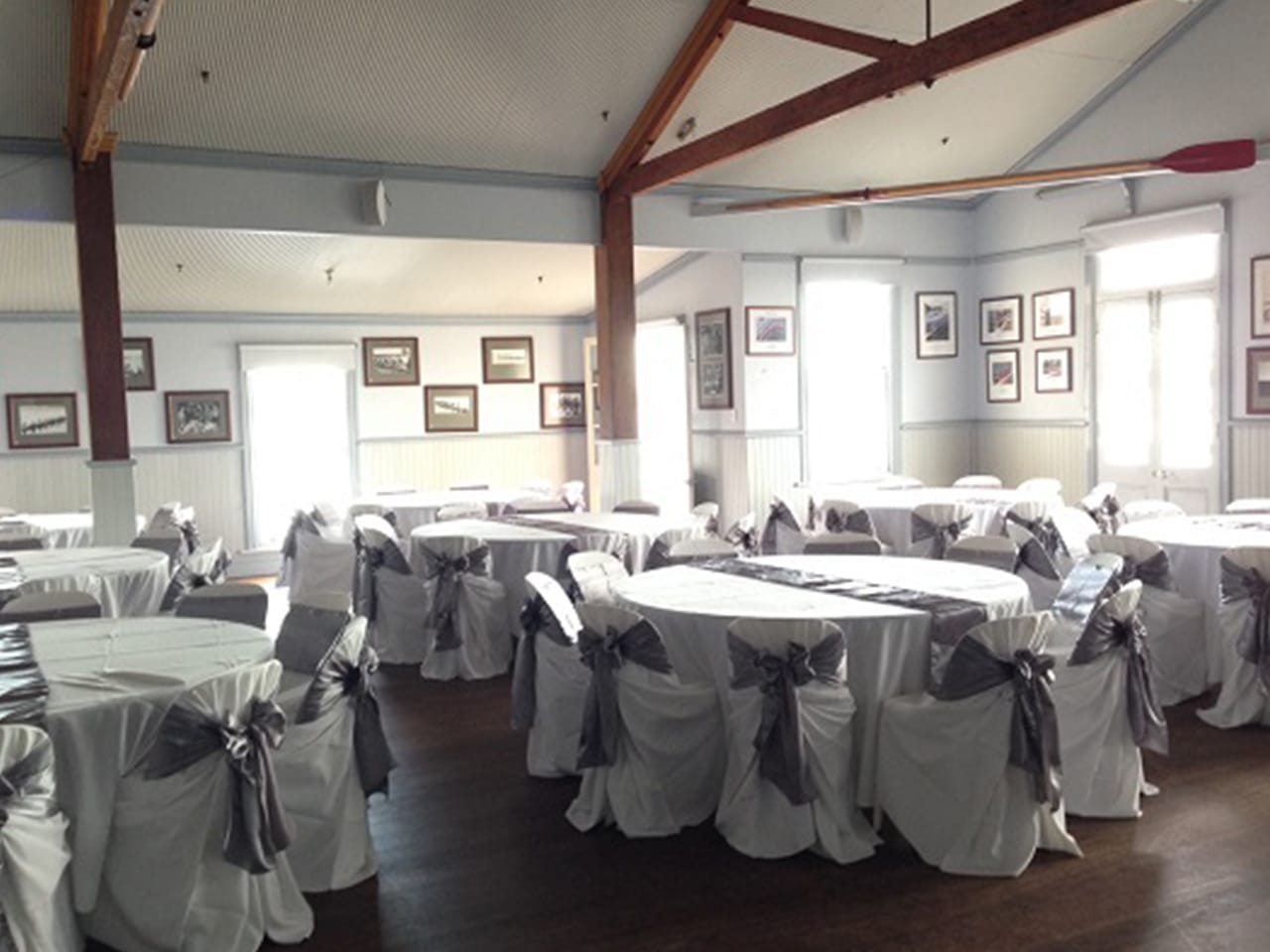 Chairs And Tables In Banquet Style Inside The Function Room With Picture Frames On The Wall