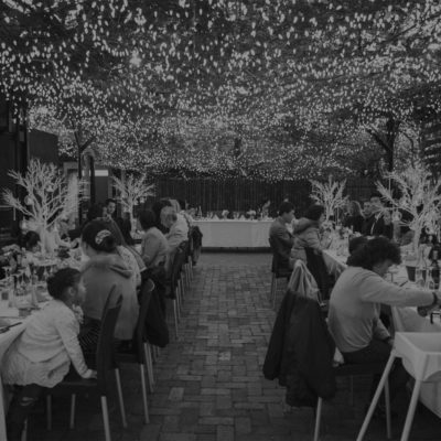 Guests Seated In Long Tables In The Open Air Function Space With String Lights Above Them