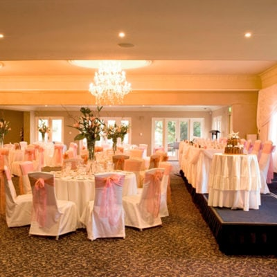 Long Table, Cake Table On Stage And Banquet Style Setup Inside The Function Room With Chandeliers