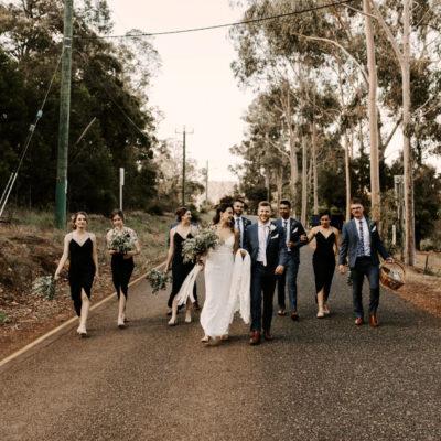 Bridal party walking forward a country road