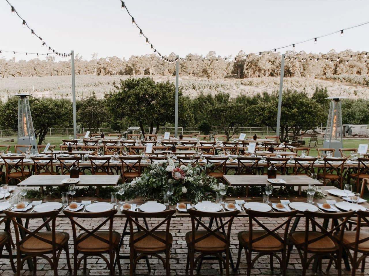 Empty long tables and seats set out for a wedding reception