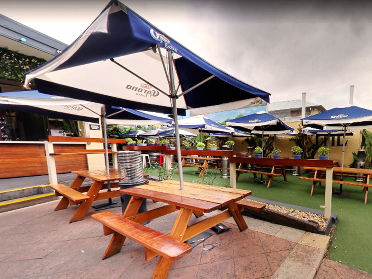 Wooden Tables And Chairs With Umbrellas And Green Plants In The Outdoor Function Venue