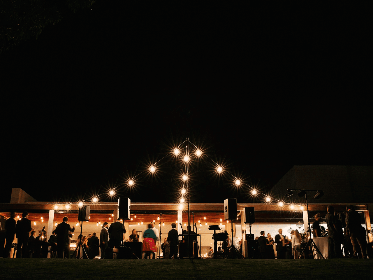 Guests Enjoying The Evening Outside The Function Room With String Lights