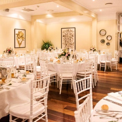 Indoor wedding room setting with round white tables