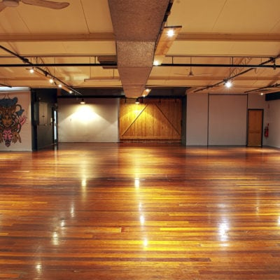 Empty warehouse with polished wooden floors and barn door exit