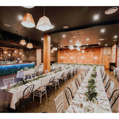 The Gallery set up for wedding with long white tables with brick backdrop