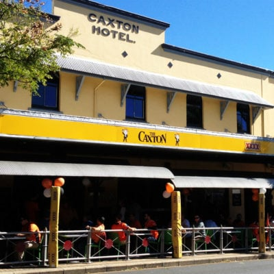 The Caxton Hotel front streetside entrance with yellow signage