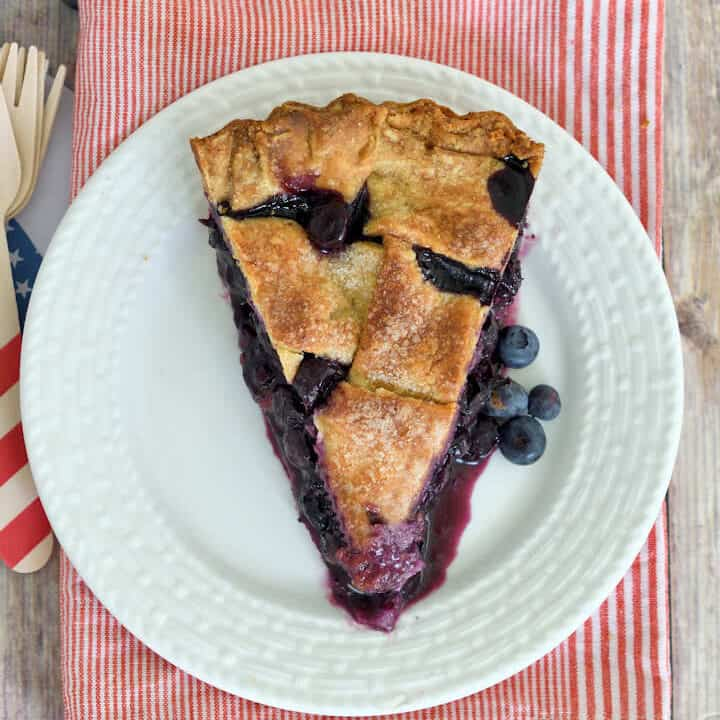 an overheat view of a slice of blueberry pie on a white plate