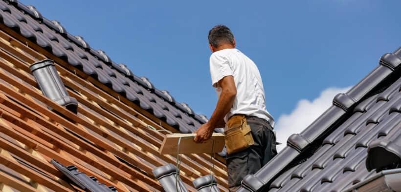 Dachdecker beim Verlegen der Dacheindeckung