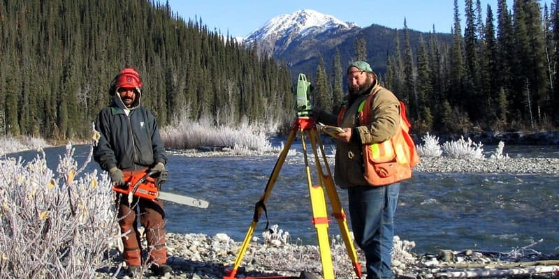 historical - field survey crew with total station and chainsaw