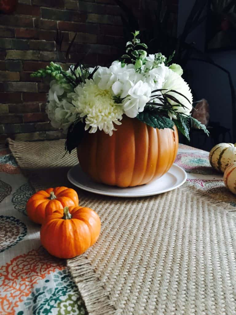 thanksgiving floral centerpiece. Pumpkin vase filled with flowers