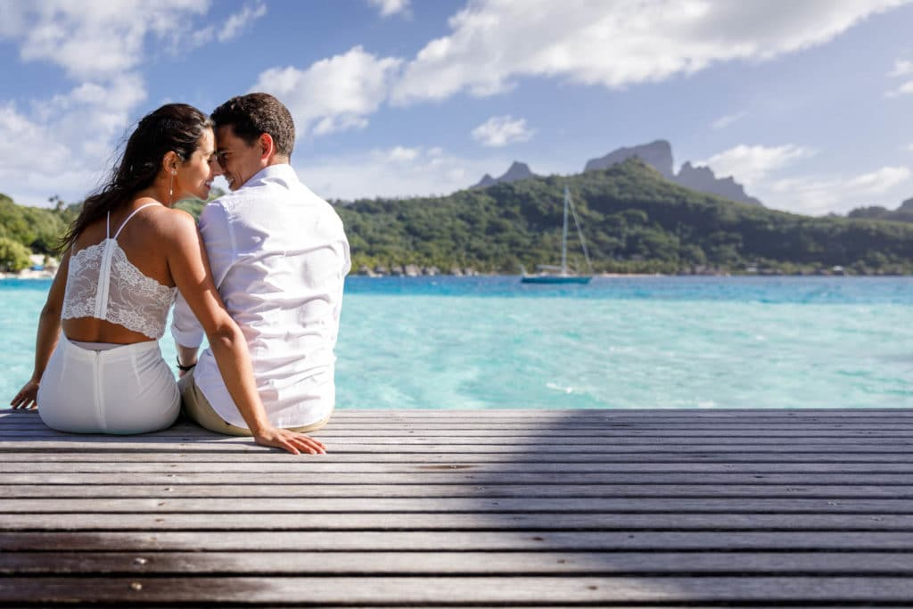 Livia & Marc sitting on the deck of their overwater bungalow