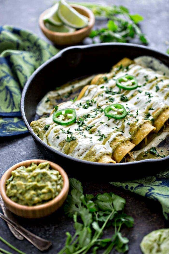 Chicken, Black Bean, and Spinach Enchiladas with Tomatillo Enchilada Sauce in cast iron skillet
